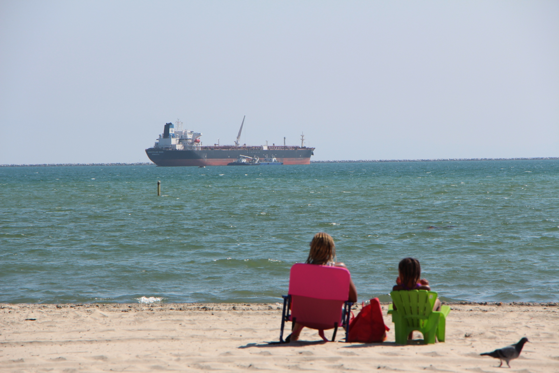 In this photo: a mother and child relax at the beach as a shipping container ship floats out in the Pacific Ocean close to shore